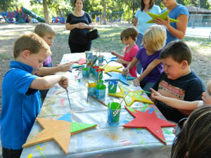 Children at Oak Park in Minot, ND, paint Stars of Hope to help their community recover from last year's devistating floods.