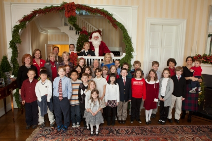 Students from White Oaks Elementary School and Major Blain's family take a picture with Santa, Dr. Jill Biden, Mrs. Patty Shinseki, Colonel Rebecca Porter and United Through Reading.