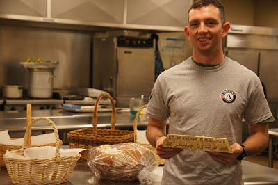 National Guard Lt. Brandon Williams takes a break from preparing bread baskets for an upcoming dinner at Our Daily Bread in Baltimore, MD.
