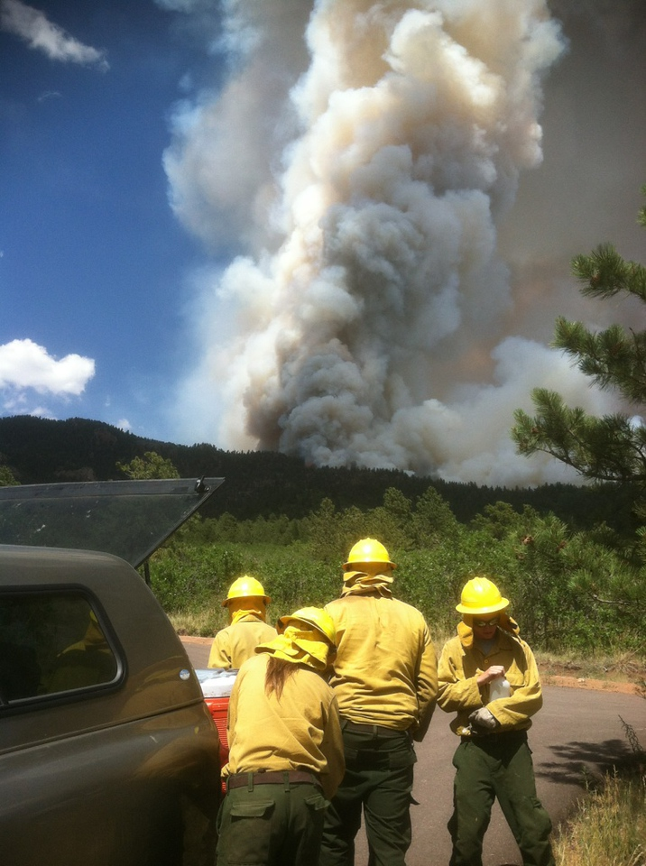 AmeriCorps NCCC members with Fire 4 gear up as a smoke column from the Waldo Canyon Fire looms in the background.