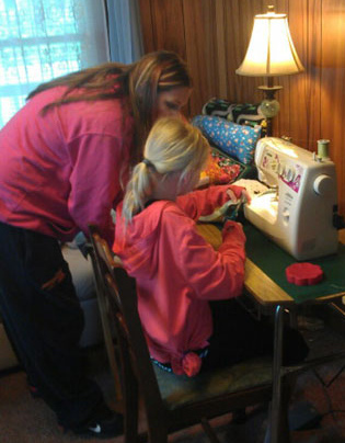 Autumn Blinn is joined by her mother, Kara Snell, while making therapeutic pillows in their home.