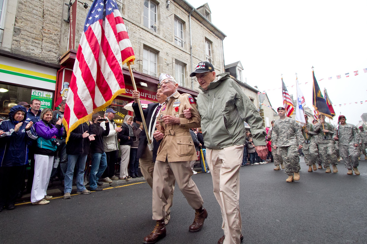 Zane Schlemmer, a veteran U.S. Army paratrooper who jumped into northern France as a sergeant with the 82nd Airborne Division, walks in his jump boots down the main street of Sainte Mere Eglise with other World War II veterans during the 67th anniversary of the Allied invasion of France, June 5, 2011.  French citizens applaud as he and current paratroopers with the 82nd and other Army units parade past.  (U.S. Army photo by Sgt. Michael J. MacLeod)