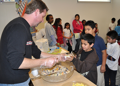 """Richard Burley, a nutritionist for the USDA Food and Nutrition Service Southwest Regional Office, serves a delicious """"fruity granola yogurt"""" treat to the children of Jubilee Center."""