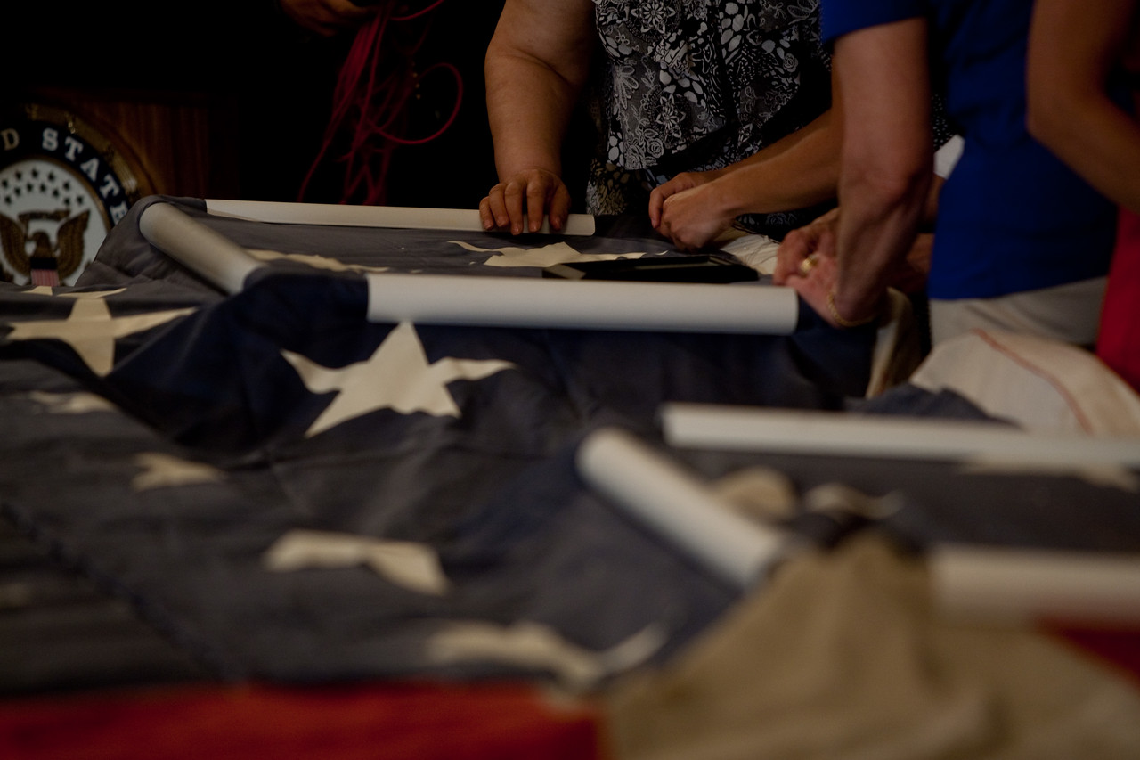 Participants add new stitches to a portion of the National 9/11 flag during a visit to Capitol Hill on July 14, 2011.