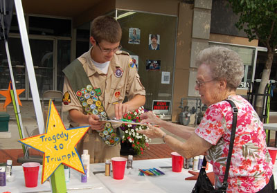 Jimmy Willerton, Centennial Eagle Scout candidate, helps his 90-year-old great grandmother sign in to paint one of the 100 Stars of Hope that his Eagle Project took to Minot, North Dakota, to help with that community's recovery from last year's floods.
