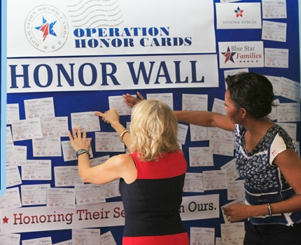At a Joining Forces event with the NASCAR foundation in Miami, First Lady Michelle Obama and Dr. Jill Biden participate in Operation Honor Cards, pledging to perform community service in honor of military families.