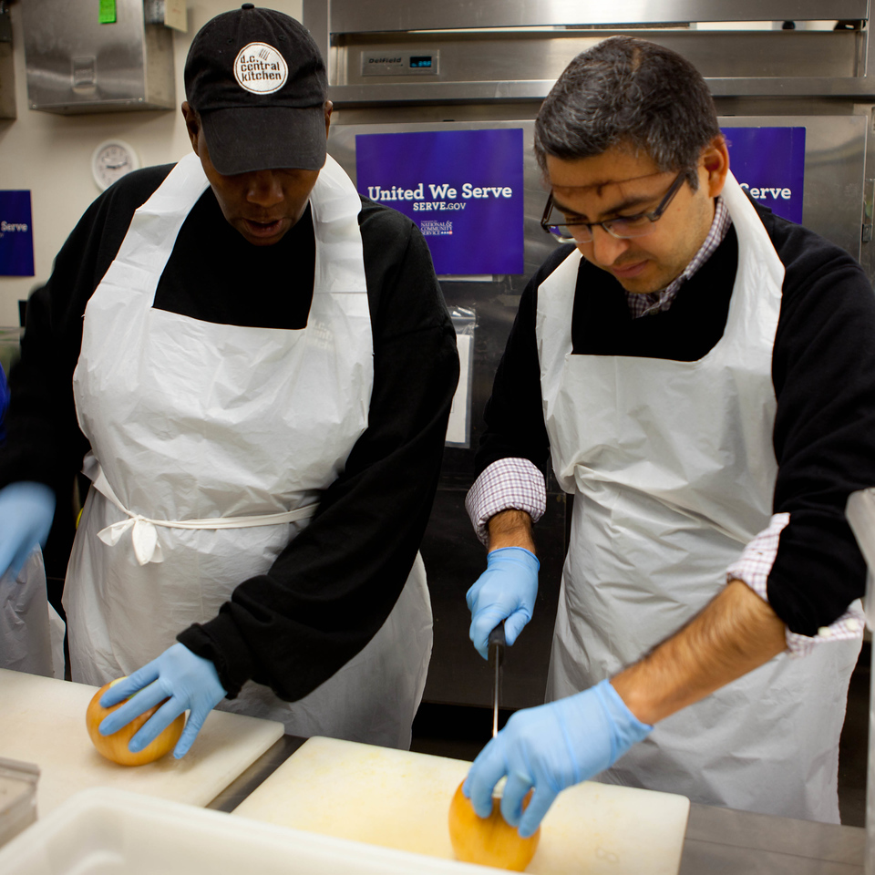 CNCS Acting CEO Robert Velasco (R) prepares to cut onions for the day's main course: fried rice with chicken and vegetables.