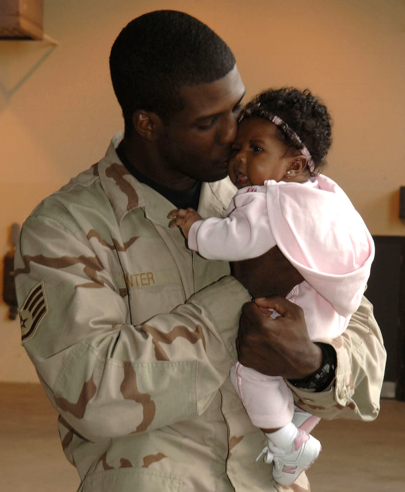 MOODY AIR FORCE BASE, Ga. - Staff Sgt. Corodney Hunter, 824th Security Forces Squadron here, holds his daughter Jamari at the security forces homecoming ceremony Thursday, Dec. 14, 2006. Deployed members from the 820th Security Forces Group, 23rd SFS and Texas Air National Guard returned home early from their deployment in order to spend the holidays with family and friends. USAF photo by Airman 1st Class Elizabeth Rissmiller
