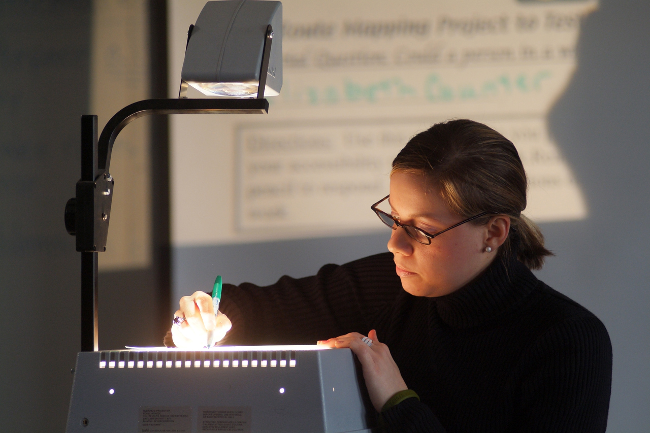 A teacher writes notes on an overhead projector during class in this CNCS file photo.