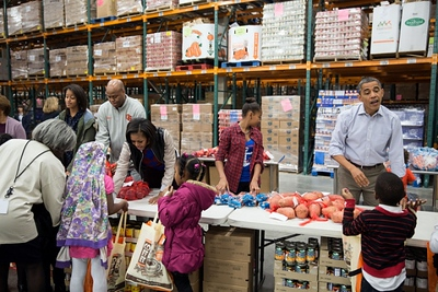 President Barack Obama, along with First Lady Michelle Obama, daughters Sasha and Malia, and Craig Robinson, participates in a service project at the Capital Area Food Bank in Washington, DC, Nov. 21, 2012. (Official White House Photo by Pete Souza)