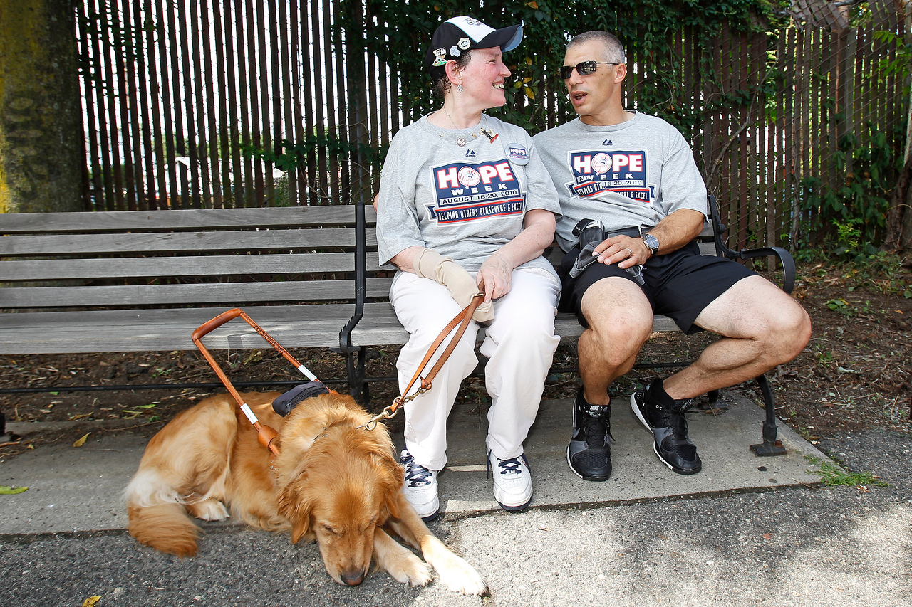 Yankees Manager Joe Girardi and honoree Jane Lang (and her dog Clipper) wait for a train to take them to Yankee Stadium for the evening's Yankee game.