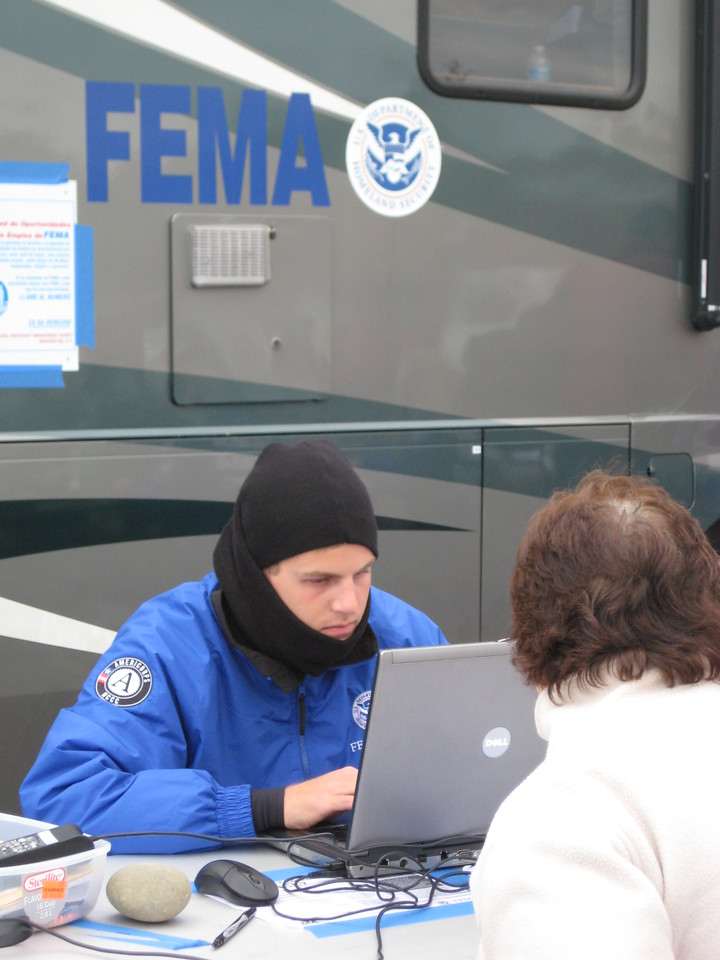A FEMA Corps member assists a Hurricane Sandy survivor at a mobile Disaster Recovery Center in Brick Township, NJ, on Nov. 4, 2012. FEMA is working with local and state officials to assist residents affected by Hurricane Sandy. (Photo by Mike McCormick/FEMA)