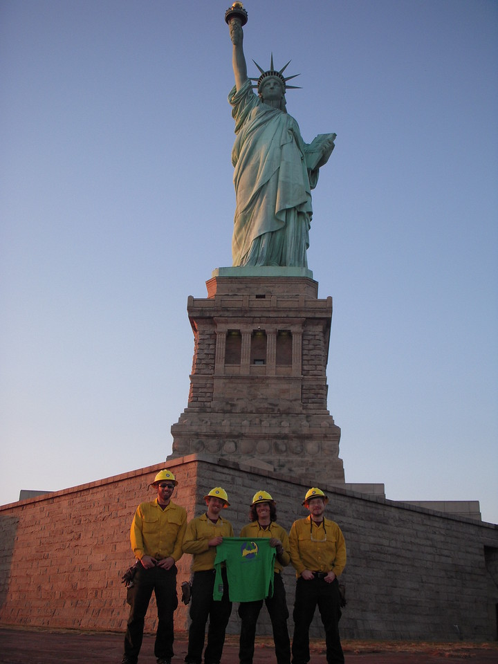 AmeriCorps Cape Cod members working on the Liberty Island cleanup pause to pose before the Statue of Liberty.