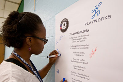 Rebbecca Bakre, one of the new 22 Playworks Baltimore and DC AmeriCorps members, signs the AmeriCorps pledge at Federal Hill Preparatory school in Baltimore, MD. (Photo By Scott Julian)