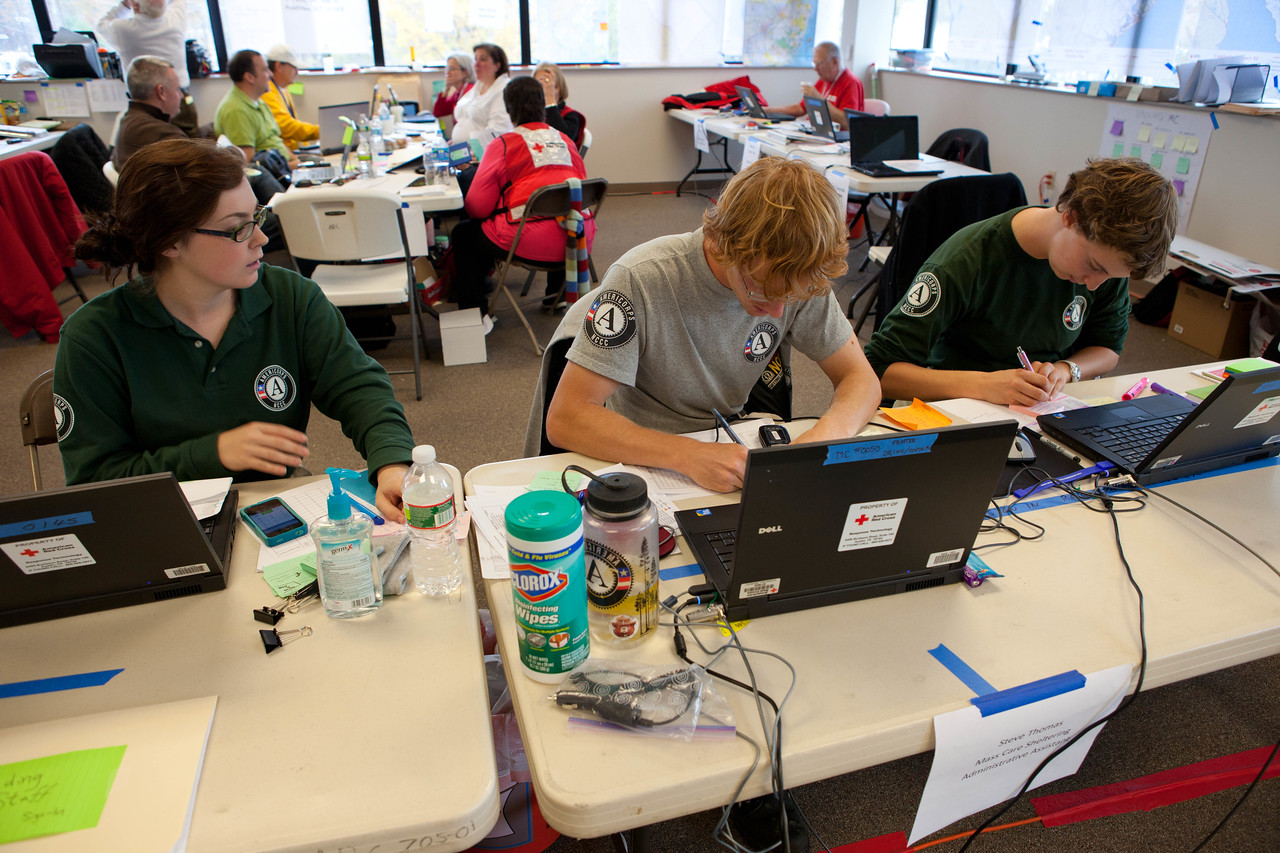Three AmeriCorps NCCC members serve inside a call center at the Red Cross headquarters in North Brunswick Township, NJ. (Corporation for National and Community Service photo)