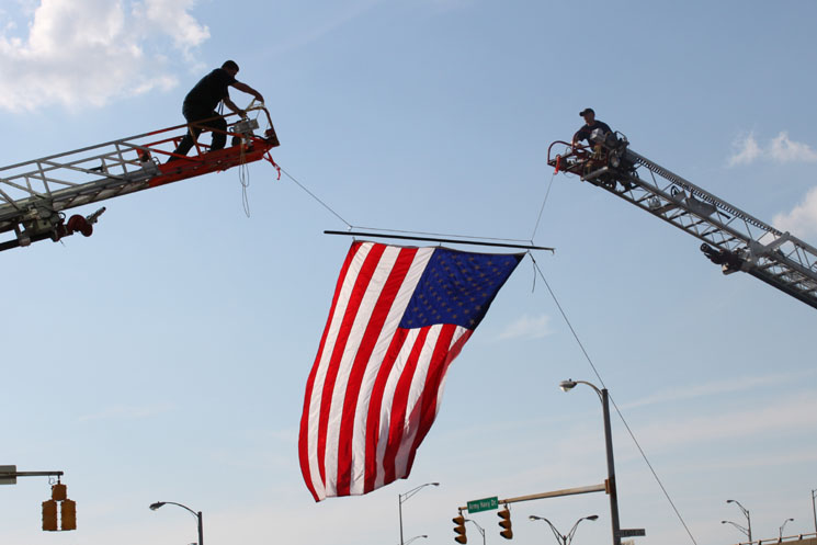 Firefighters fly an American flag by suspending it between two ladder trucks. Photo courtesy of Ron Patterson.