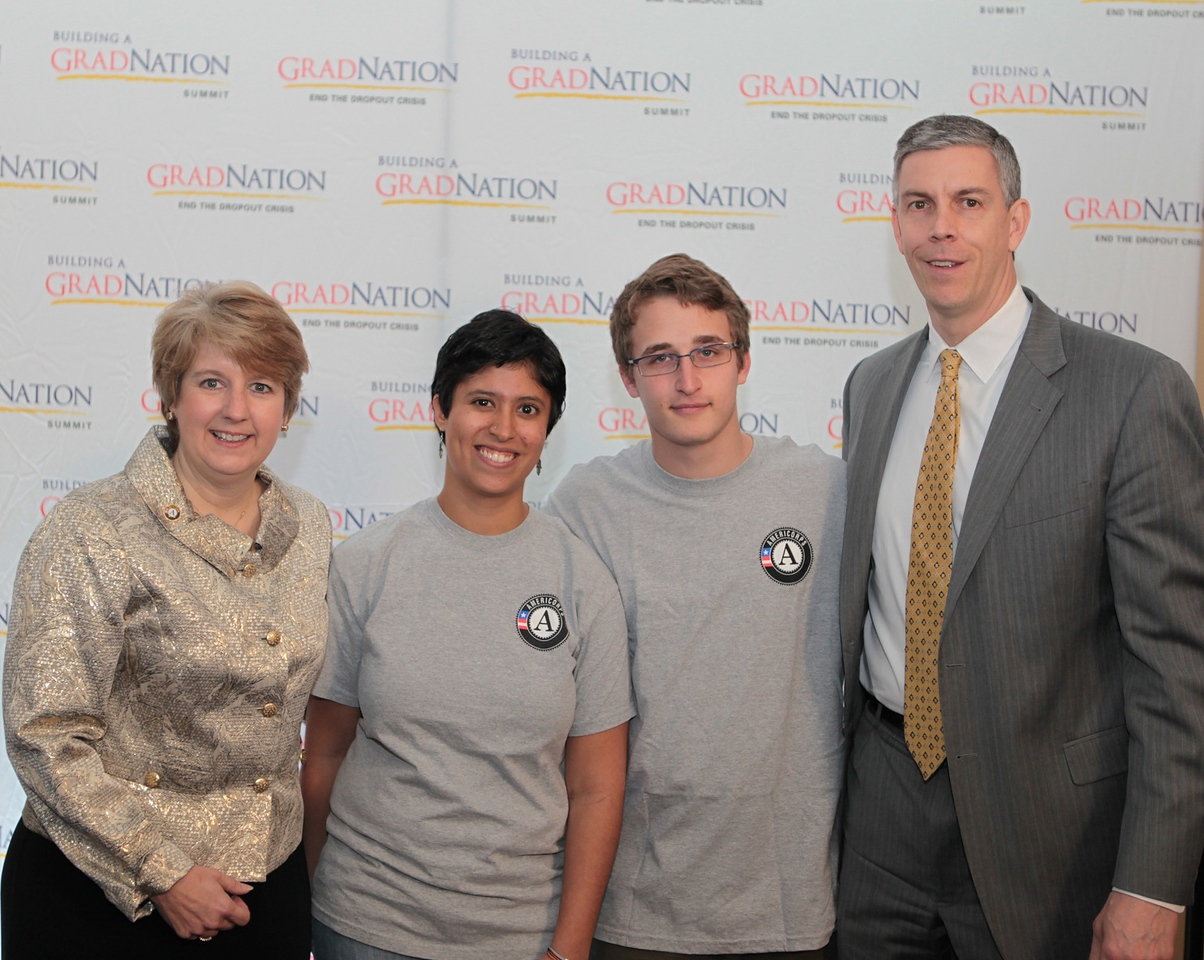 Corporation for National and Community Service CEO Wendy Spencer (left) and U.S. Secretary of Education Arne Duncan (right) pose with two AmeriCorps members during the Grad Nation Summit in Washington, DC, on Feb. 25, 2013.
