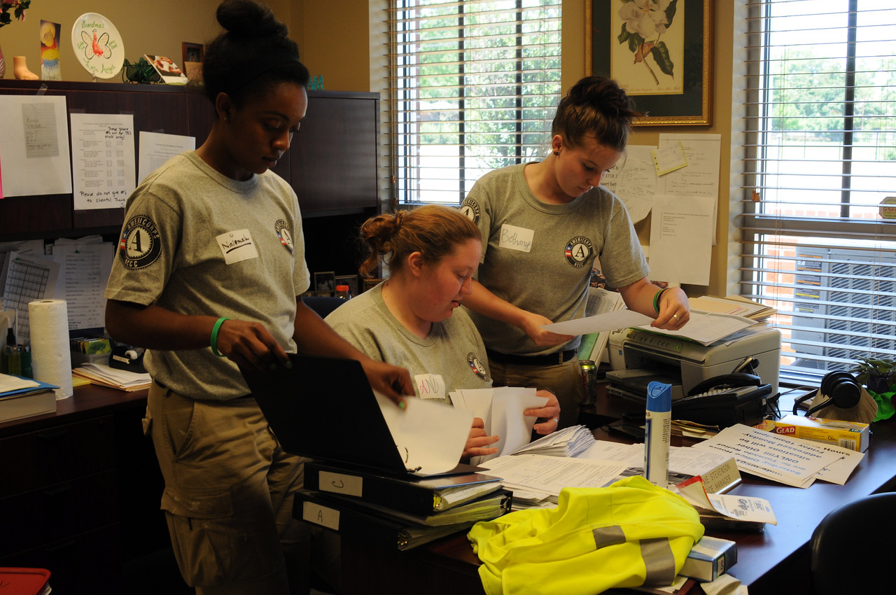 Tuscaloosa, AL, May 28, 2011 -- AmeriCorps NCCC Workers Naiemah Brown, Andrea Zeritis, and Bethany Fourner process requests for disaster assistance at a charitable thrift store warehouse.  AmeriCorps is an important FEMA partner in responding to disasters such as the deadly April tornado.   George Armstrong/FEMA