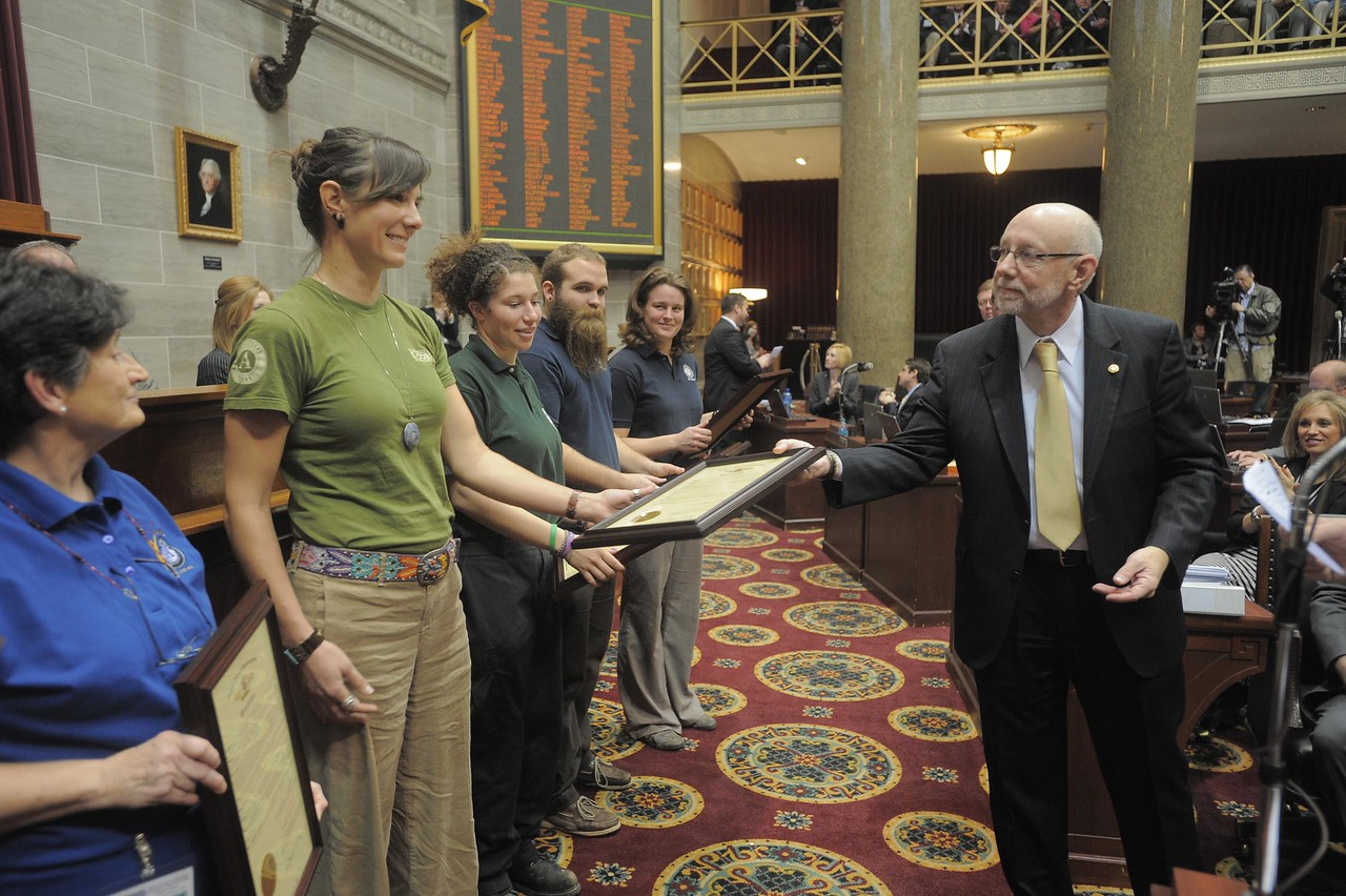Megan Helton, in green, receives a copy of Missouri House Resolution No. 244, recognizing the work of AmeriCorps in Joplin, MO.