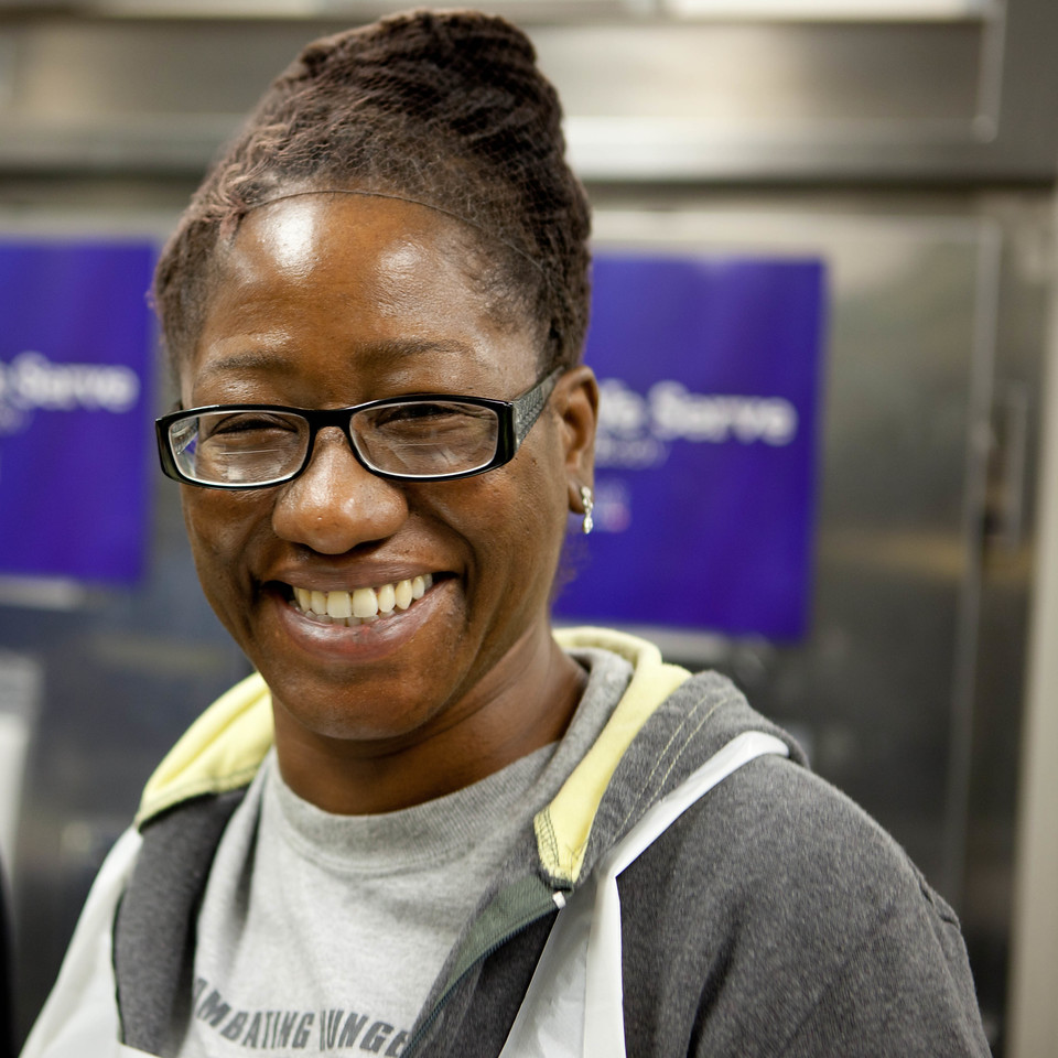DC Central Kitchen employee smiles as she prepares ingredients for the day's meal.