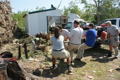 NCCC Corps Members remove debris from a resident's home in Leakesville, MS.