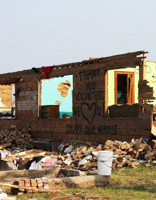 A spray-painted Thank You Volunteers was left on the wall of a home that was mostly destroyed by the tornadoes that struck Joplin, MO, in 2011.