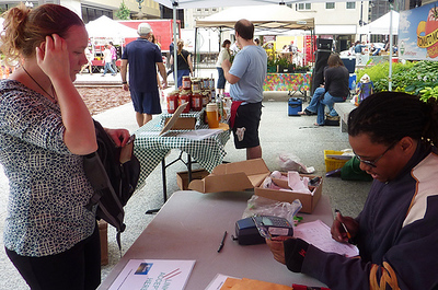 Corey Chapman, EBT Coordinator for City of Chicago farmers markets, processes a woman's benefits card so she can purchase items at the market.