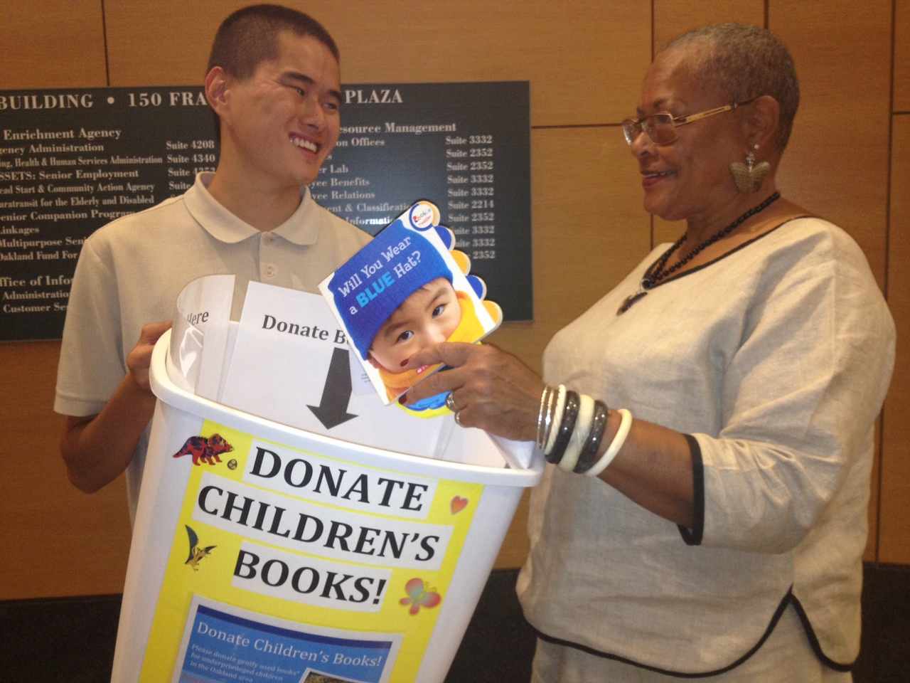 Michael Wang collects a children's book from Ethel Parks, a Foster Grandparent, on the first day of the Summer Book Drive in Oakland, CA.