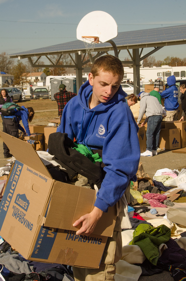 FEMA Corps member John Styles carries a box of donated clothes to be sorted at Union Beach Memorial Middle School in New Jersey on November 6, 2012. Residents here have opened up their hearts and donations have been flooding the drop-off sites. (Photo by Liz Roll/FEMA)