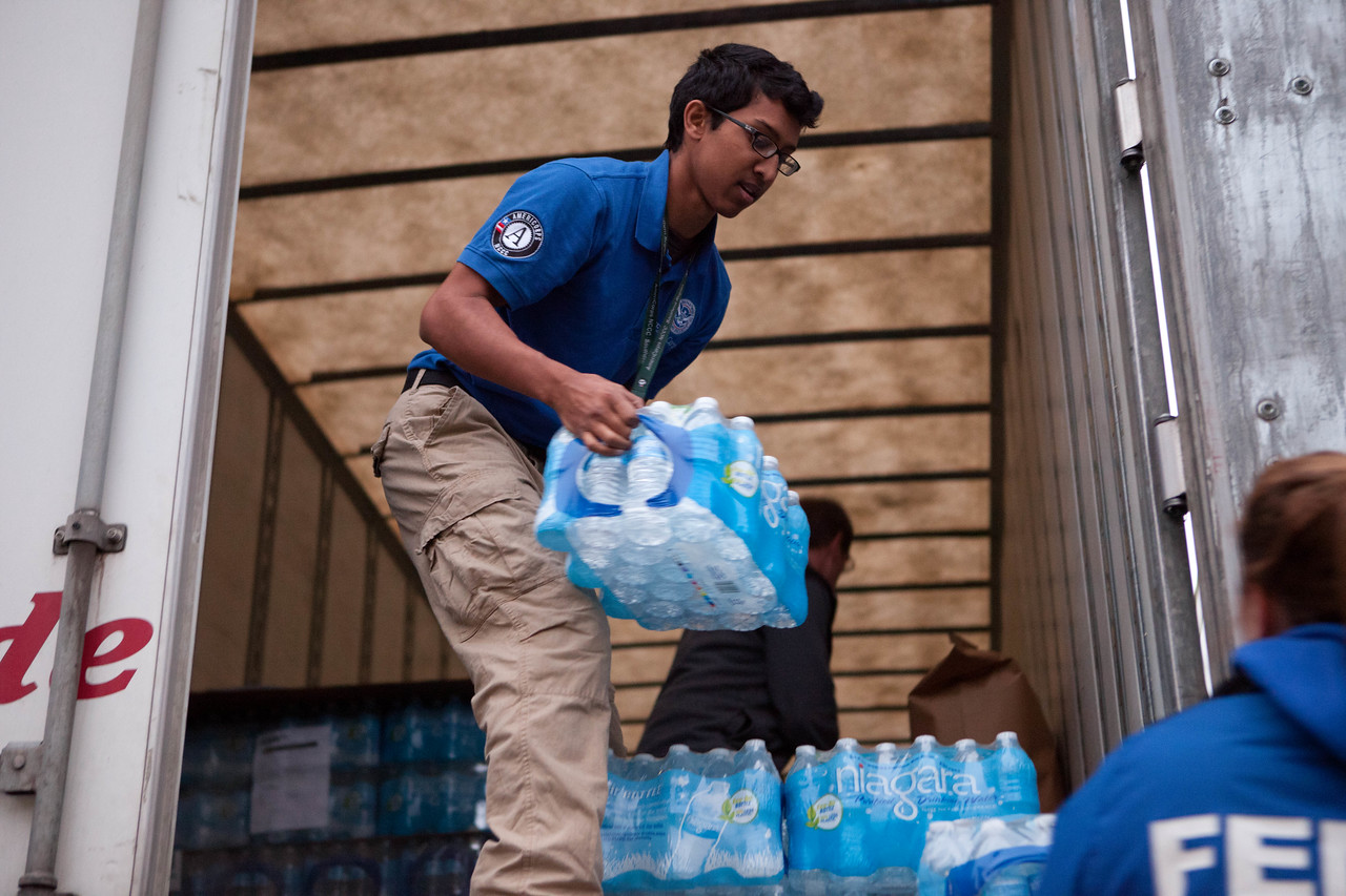 A member of FEMA Corps unloads water from a supply truck in Far Rockaway, NY. (Corporation for National and Community Service photo)