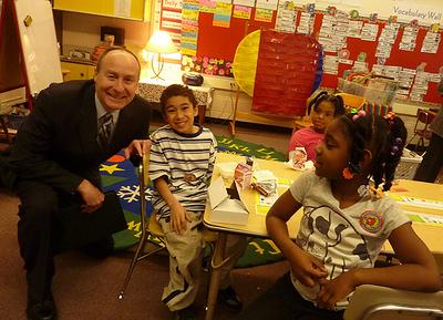 Tim English with three kids – Deputy Regional Administrator Tim English with three students eating breakfast.
