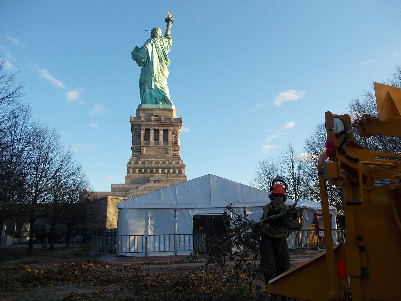 An AmeriCorps Cape Cod member feeds branches into a wood chipper during cleanup efforts on Liberty Island.