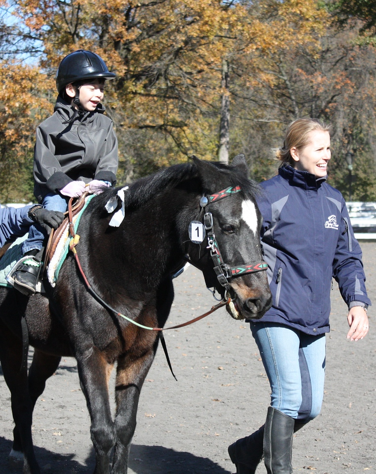 Flying Manes founder Stefanie Dwyer leads one of the students during a therapeutic horse riding session.