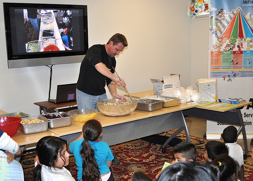 Richard Burley, a nutritionist for the USDA Food and Nutrition Service Southwest Regional Office, prepares a healthy snack of fruit, granola and low fat yogurt while his demonstration is broadcast on a screen behind him.