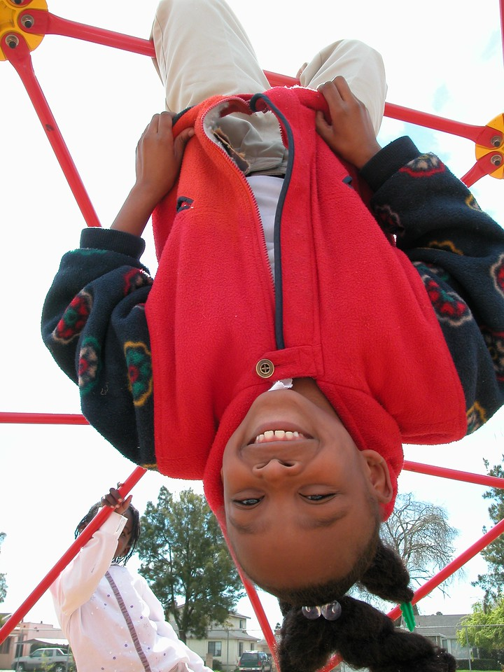 A girl plays upside down on a KaBOOM! built playground. (Photo courtesy KaBOOM!)