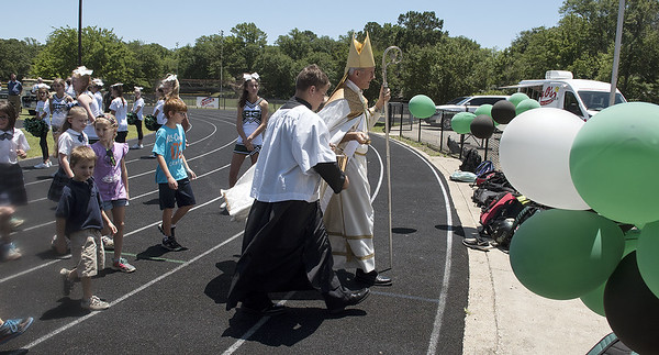 Most Rev. Joseph E. Strickland, Bishop of the Diocese of Tyler, is surrounded by St. Gregory students as he walks to the field house to bless the ground for the Brodnax Family Crusader Center at Bishop Thomas K. Gorman Cathedral School. The 4.9 million dollar multi-purpose building will replace the existing field house. It will house locker rooms, a weight room, an area for drill, dance and cheer teams and to view films.   (Sarah A. Miller/Tyler Morning Telegraph)