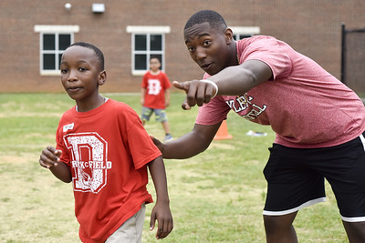 Royland Black gives Tony Cooks, 9, direction during a football game during Sports Day hosted by Robert E. Lee students at Douglas Elementary School in Tyler, Texas, on Friday, May 19, 2017. The event was organized in part by teacher Mrs. Jones and her son Royland Black as a way to motivate and reward students for their hard work at the end of the school year. (Chelsea Purgahn/Tyler Morning Telegraph)