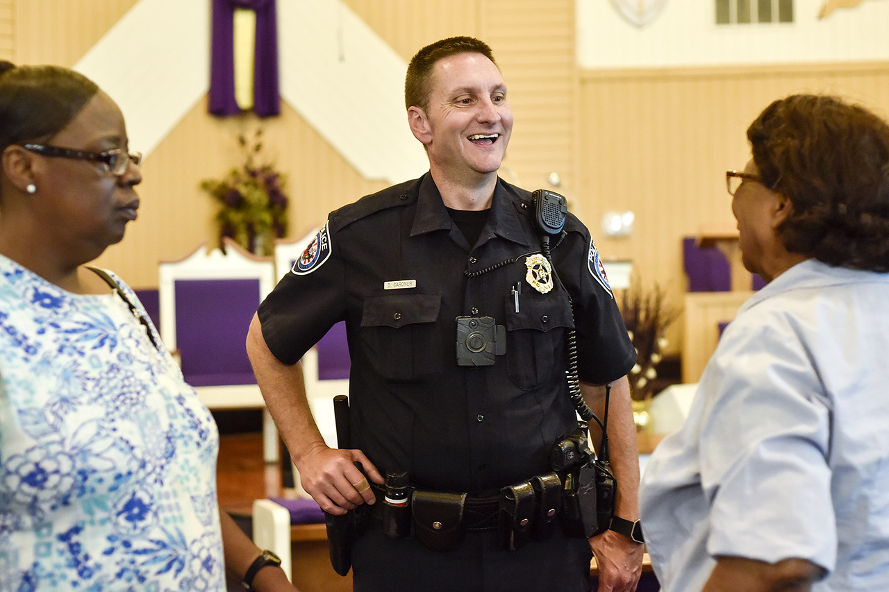 Officer Darrell Gardner laughs as he chats with Phyllis Waters, left, and Jerlean Hudson, right, during a community meeting at Smith Temple Church of God in Tyler, Texas, on Tuesday, May 30, 2017. Gardner has worked the same beat for over 18 years. He has established a relationship with the citizens who call him directly when things are not right in their neighborhoods. (Chelsea Purgahn/Tyler Morning Telegraph)