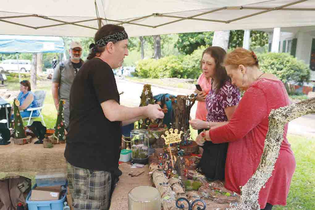 "David Carley, vendor and founder of the ""My Eye on Art"" jewelry shop in Ben Wheeler, speaks to customers at his booth during the annual Tyler Celtic Festival on the grounds of the Goodman-LeGrand House & Museum on Saturday. (Schuyler Wick/Staff)"