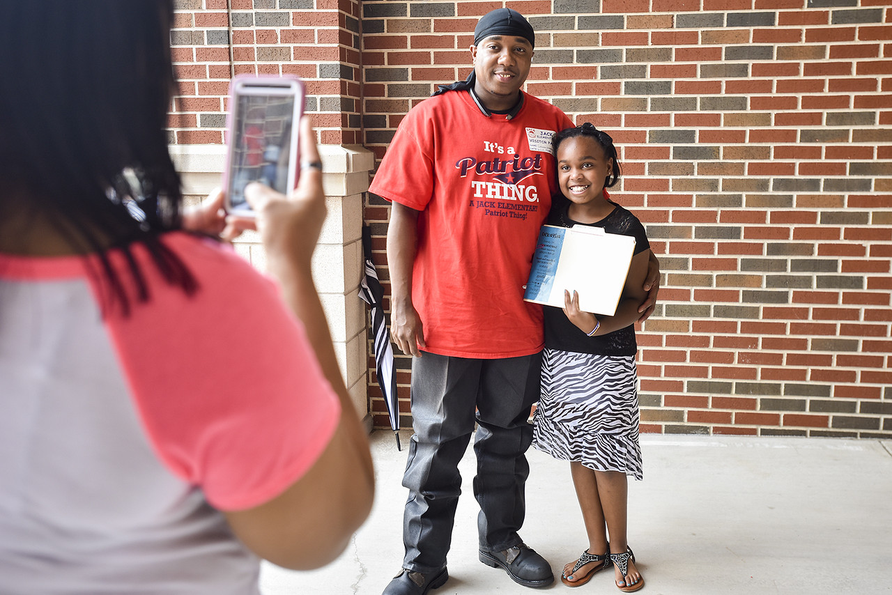 Lakeshi Stanley takes a picture of Dekova Stanley and Dekaysia Stanley, 11, during a sendoff for fifth graders at Jack Elementary School in Tyler, Texas, on Friday, June 2, 2017. The school has hosted the special sendoff for the fifth graders on the last day of school every year since it opened its doors in 2007. (Chelsea Purgahn/Tyler Morning Telegraph)