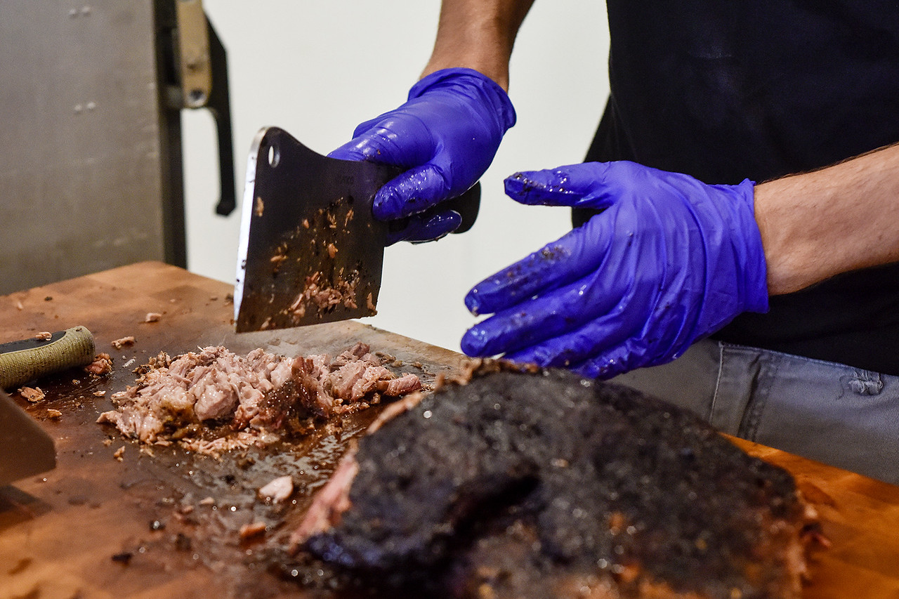 Jason Smith chops brisket at Cowburners in Mineola, Texas, on Thursday, June 1, 2017. The new restaurant features Texas barbecue staples that Jason Herring used to cook in a trailer food truck. (Chelsea Purgahn/Tyler Morning Telegraph)