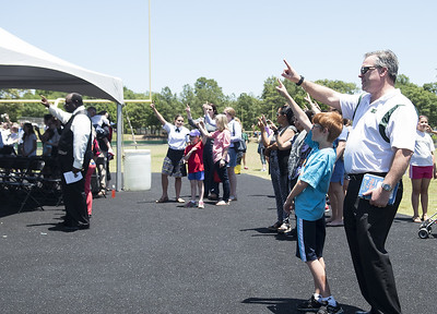 Pete Ministrelli and his son Brennan, 9, sing the school song at the ground blessing ceremony for the new Brodnax Family Crusader Center at Bishop Thomas K. Gorman Cathedral School Thursday May 25, 2017. The 4.9 million dollar multi-purpose building will replace the existing field house. It will house locker rooms, a weight room, an area for drill, dance and cheer teams and to view films.   (Sarah A. Miller/Tyler Morning Telegraph)