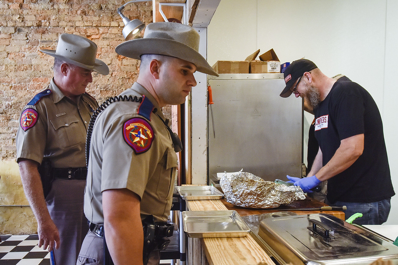 Texas Highway Patrol Officers Larry Vaughan and Justin Harrison wait at the counter as co-owner and postmaster Jason Herring chops brisket at Cowburners in Mineola, Texas, on Thursday, June 1, 2017. The new restaurant features Texas barbecue staples that Jason Herring used to cook in a trailer food truck. (Chelsea Purgahn/Tyler Morning Telegraph)