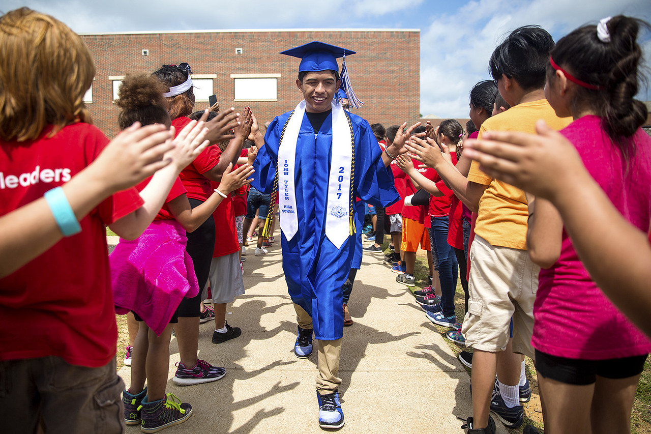A senior receives high fives from elementary students during a graduation walk honoring John Tyler High School seniors at Bell Elementary School in Tyler, Texas, on Friday, May 26, 2017. Graduating seniors participate in the event to inspire younger students to work hard and continue pursuing education. (Chelsea Purgahn/Tyler Morning Telegraph)