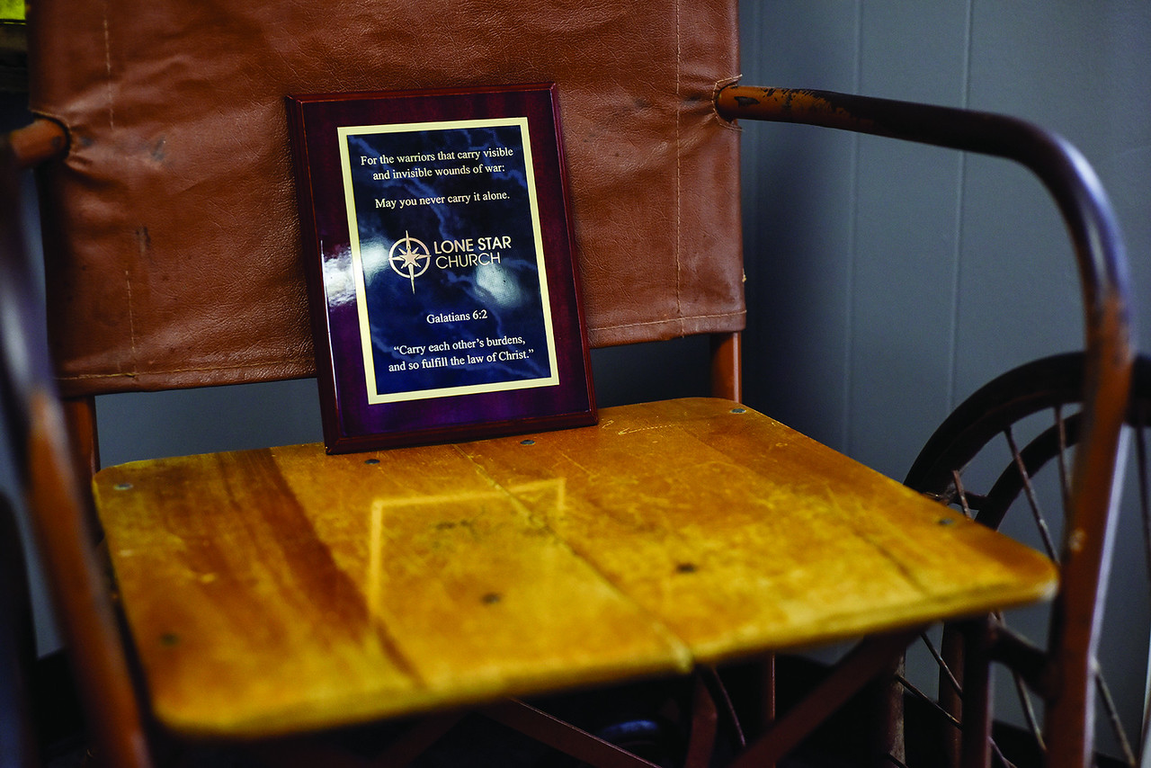 A plaque dedicated to warriors sits in an old wheelchair at Lone Star Church in Tyler, Texas, on Thursday, June 1, 2017. The church ministers to veterans and first responders, and is specifically ministering to those who have PTSD. (Chelsea Purgahn/Tyler Morning Telegraph)