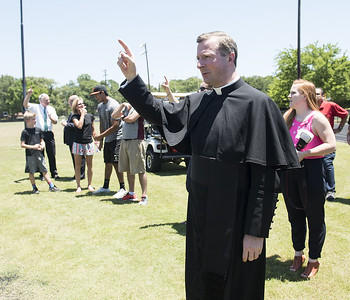 Very Rev. Dr. Anthony McLaughlin, sings the school song at the ground blessing ceremony for the new Brodnax Family Crusader Center at Bishop Thomas K. Gorman Cathedral School Thursday May 25, 2017. The 4.9 million dollar multi-purpose building will replace the existing field house. It will house locker rooms, a weight room, an area for drill, dance and cheer teams and to view films.   (Sarah A. Miller/Tyler Morning Telegraph)