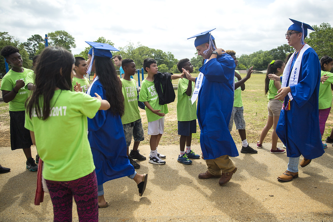 Seniors receive high fives from elementary students during a graduation walk honoring John Tyler High School seniors at Bell Elementary School in Tyler, Texas, on Friday, May 26, 2017. Graduating seniors participate in the event to inspire younger students to work hard and continue pursuing education. (Chelsea Purgahn/Tyler Morning Telegraph)