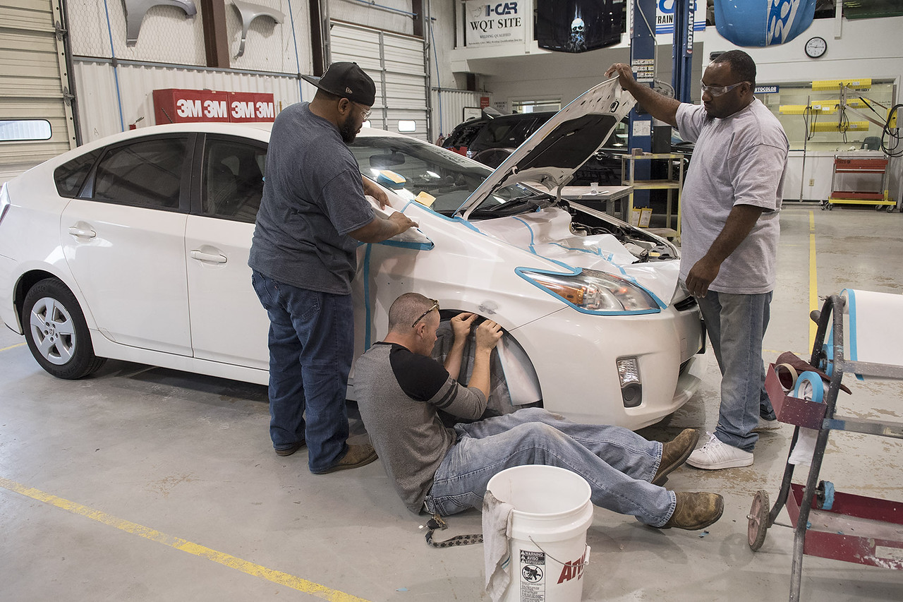 Bronte Elder, Nate Williams and Aaron Mitchell mask off a Toyota Prius as prep for primer application during class at Kilgore College's auto body shop  Monday May 17, 2017.  (Sarah A. Miller/Tyler Morning Telegraph)