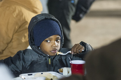A young boy eats during Hunger for Love's 7th Annual Christmas Under the Bridge on Saturday, Dec. 16, 2017 in Tyler, Texas. (Cory McCoy/Staff)