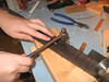 Tapping the end of the fret in place before pressing in place.